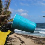 Gelber Handschuh hält blauen Plastikbecher