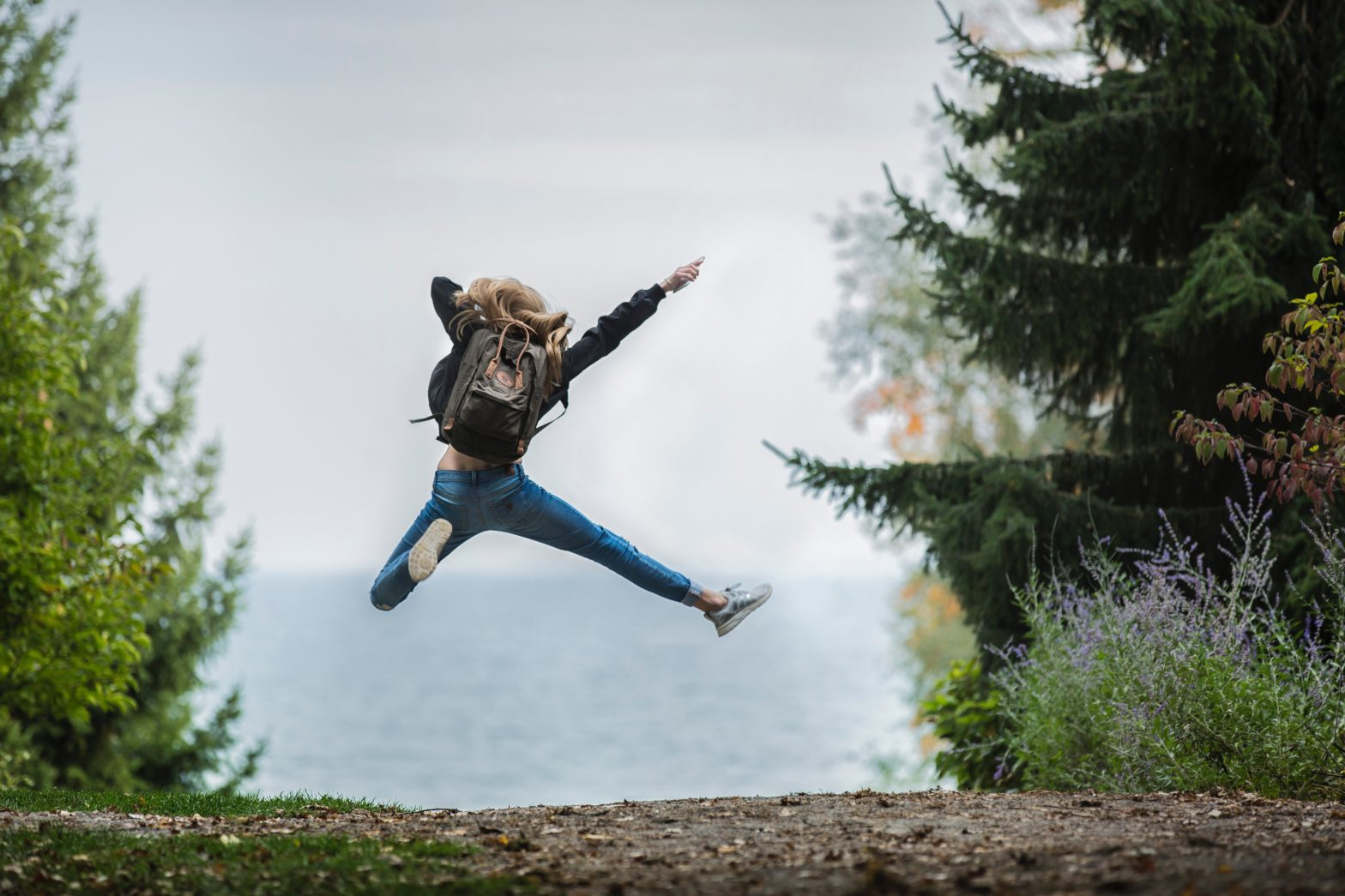 Blondes Mädchen mit Rucksack springt vor Freude