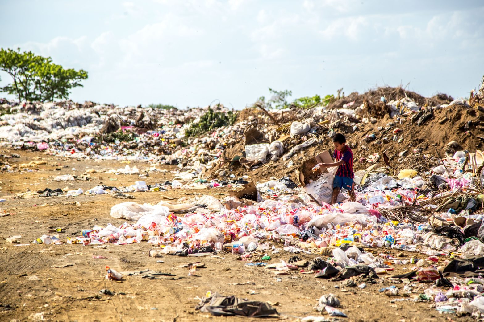 Müllberge auf welche ein Kind Plastik sammelt