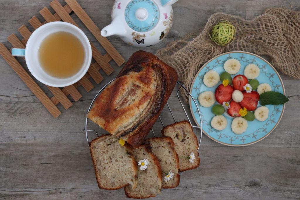 Bananenbrot mit einer Tasse Tee und Teller voller Obst