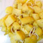 Schüssel mit Kartoffelsalat und Zwiebelringe