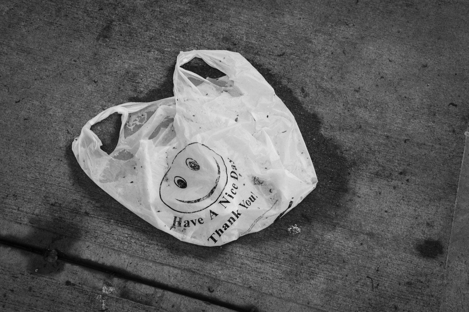 Eine dreckige, benutzte Plastiktüte mit smiley Emotikon: have a nice day