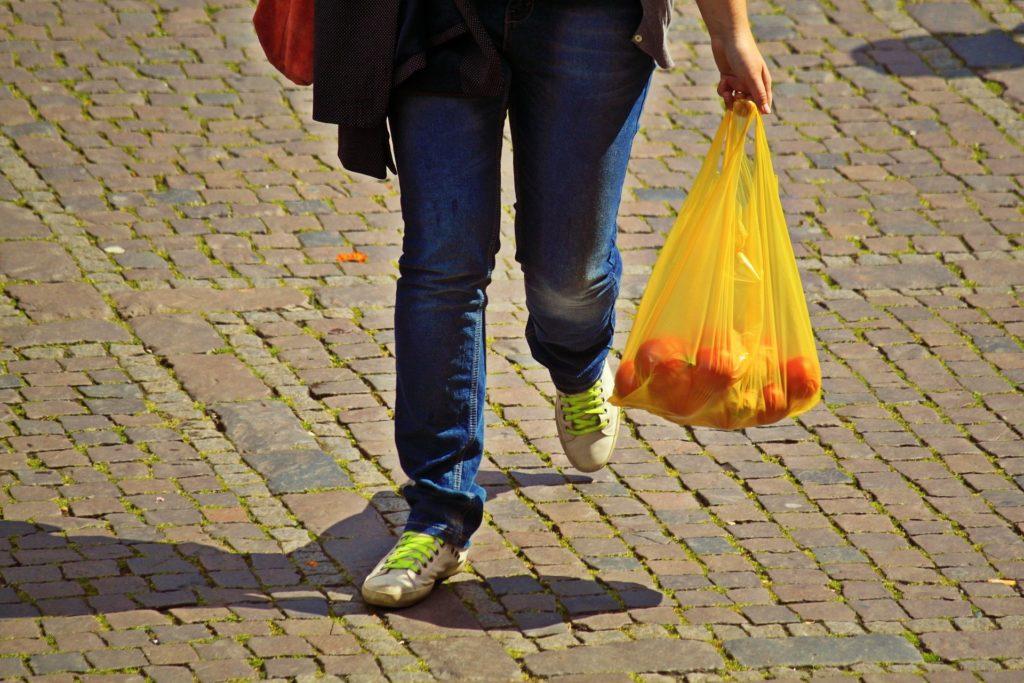 Eine Frau mit einer gelben Einwegplastiktüte