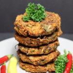 Ein Stapel von Vegane Kohlrabi & Karotten Puffer aus dem Ofen dekoriert mit Krausepetersilie und rote/gelbe Chilischoten