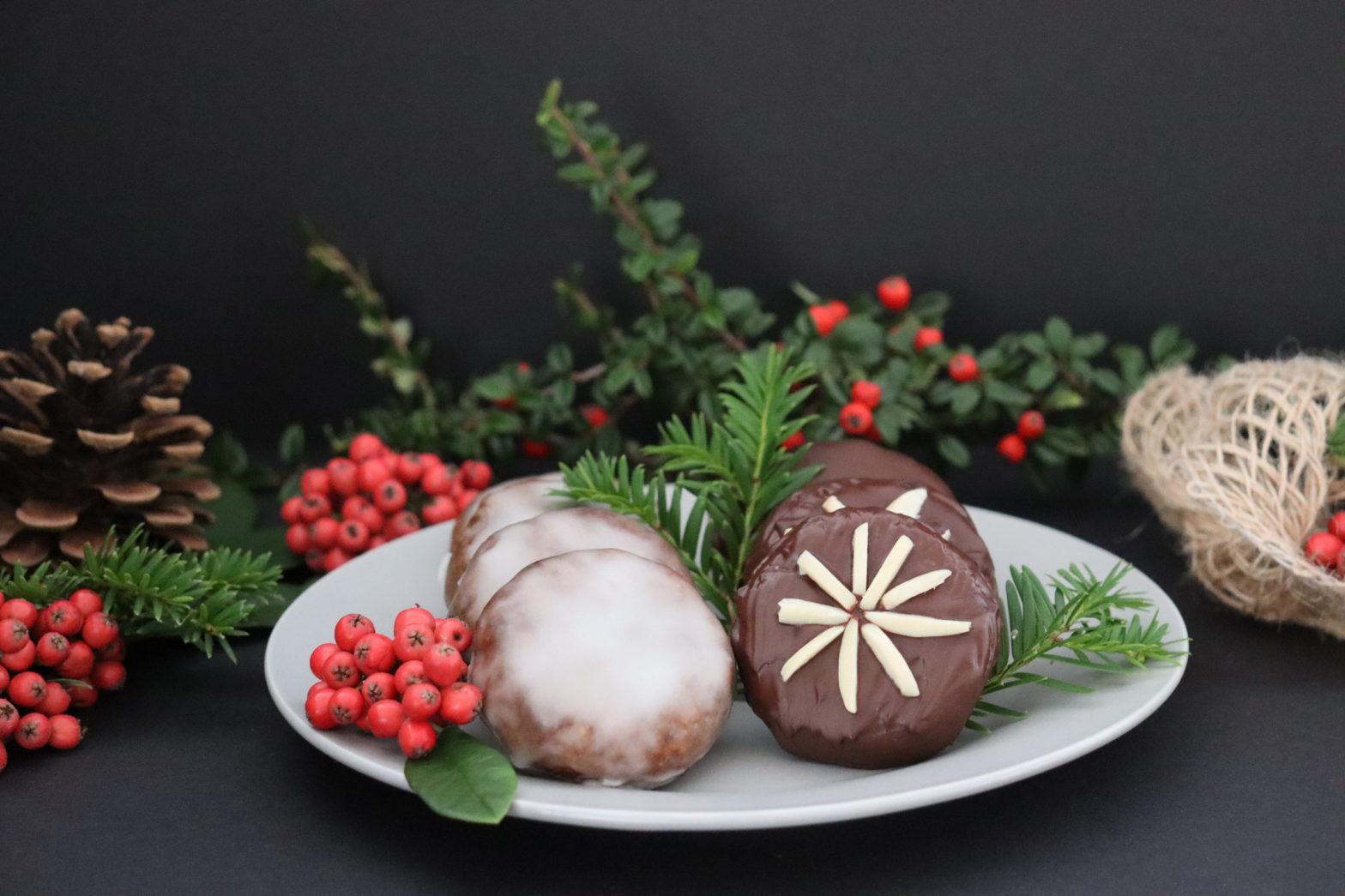 Teller mit Lebkuchen und grün-rote Weihnachtsdekoration