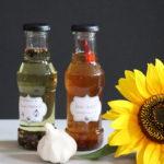 zwei Flaschen mit selbstgemachtem Knobiöl mit einer Knolle Knoblauch und Sonnenblumen