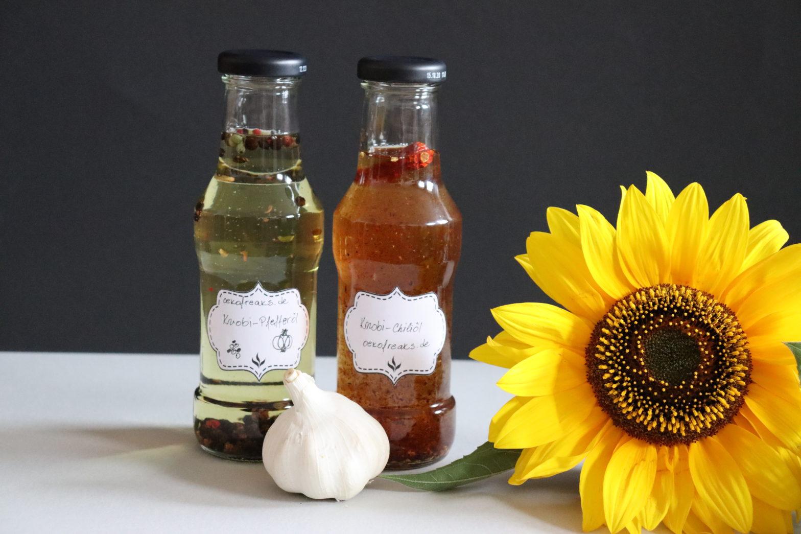 zwei Flschen mit selbstgemachtem Knobiöl und eine Knolle Knoblauch dekoriert mit Sonnenblumen