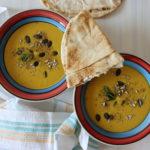 zwei Suppenschalen mit veganer Zitronensuppe dekoriert mit Körner und ein Stück arabisches Fladenbrot