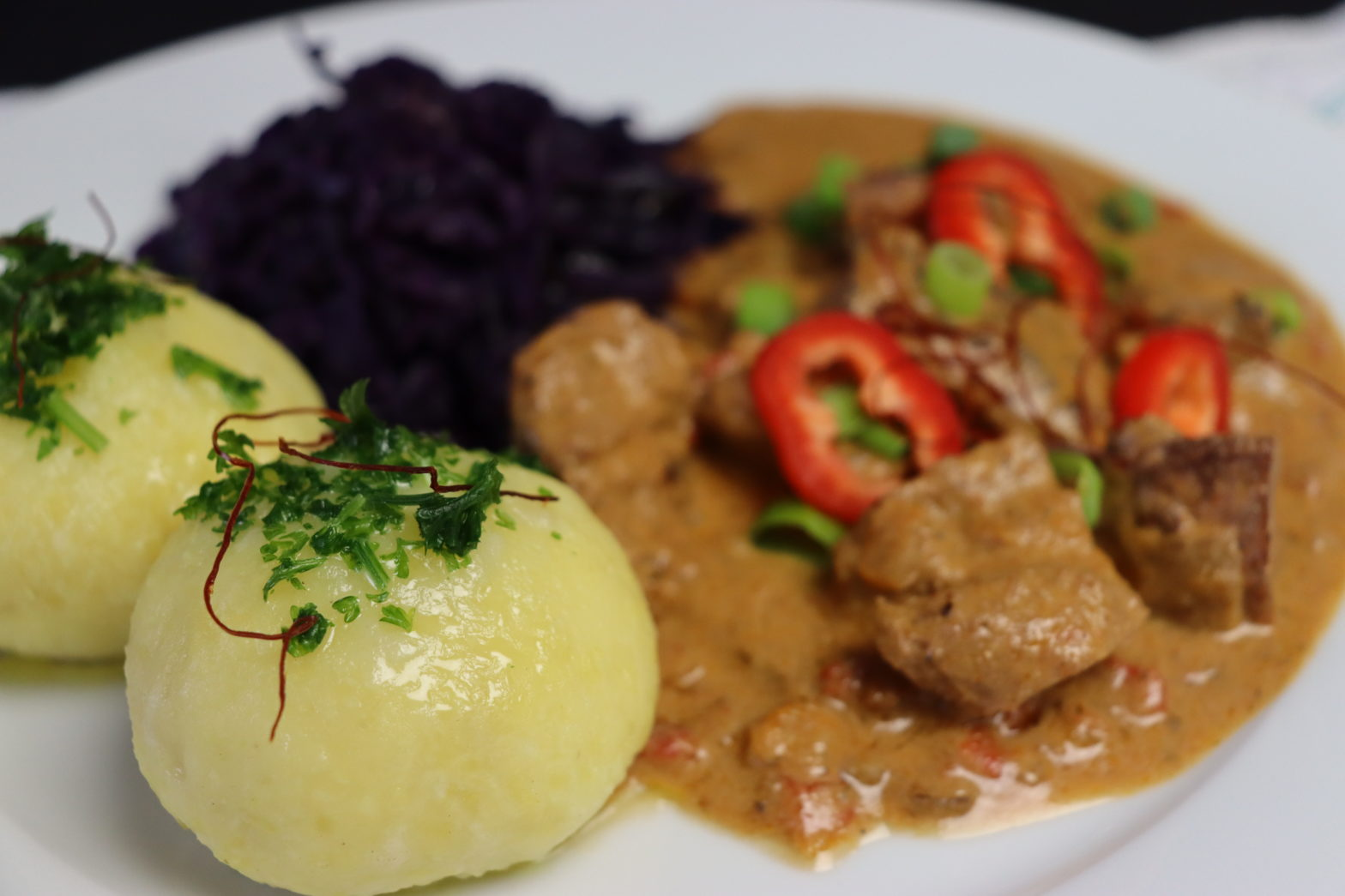 Ein Telle mit zwei Kartoffelklöße, Rotkohl und veganem Gulasch dekorirt mit rote Paprika Scheiben