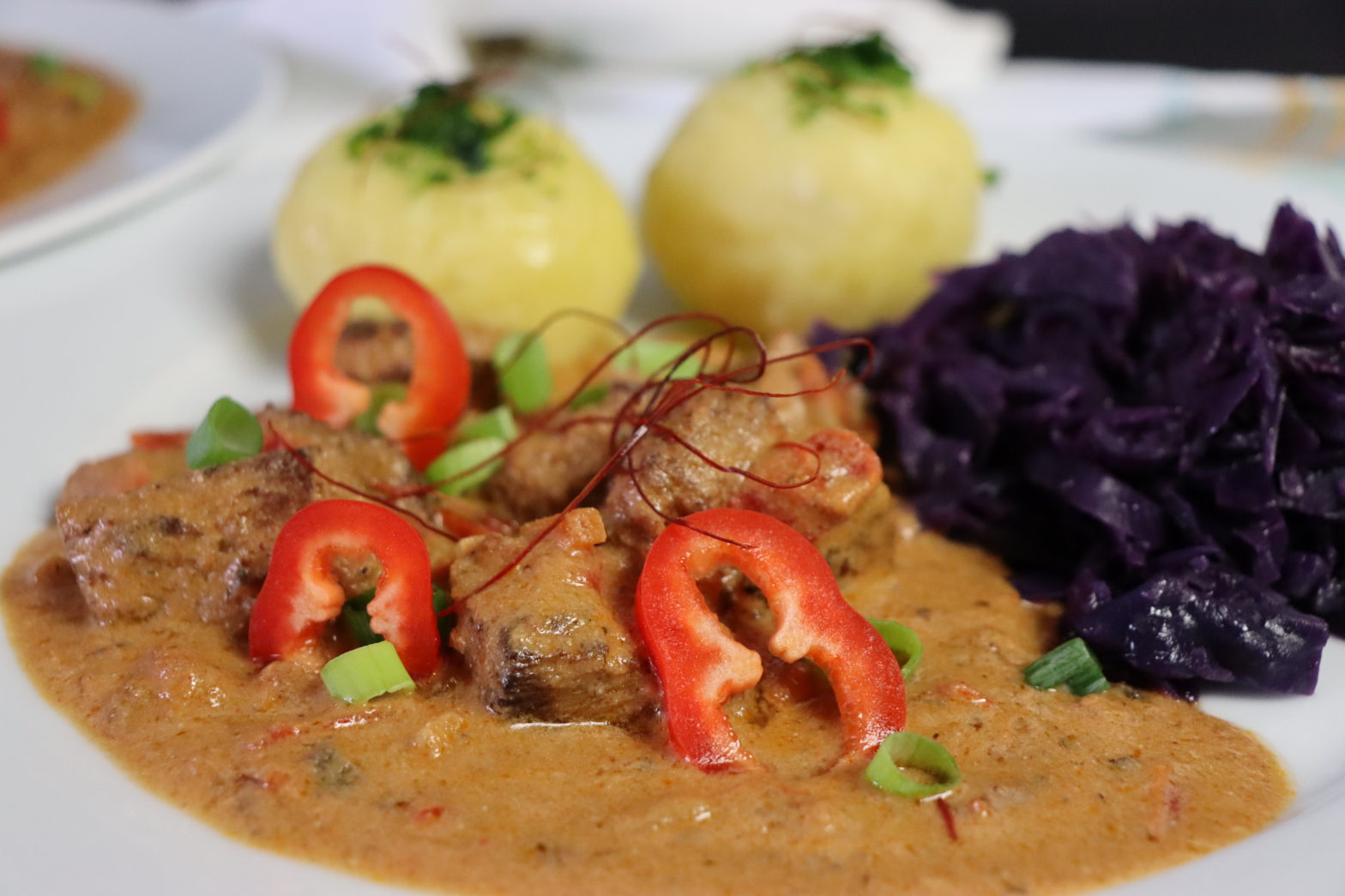 Teller mit veganem Gulasch mit Kartoffelklöße und Rotkohl