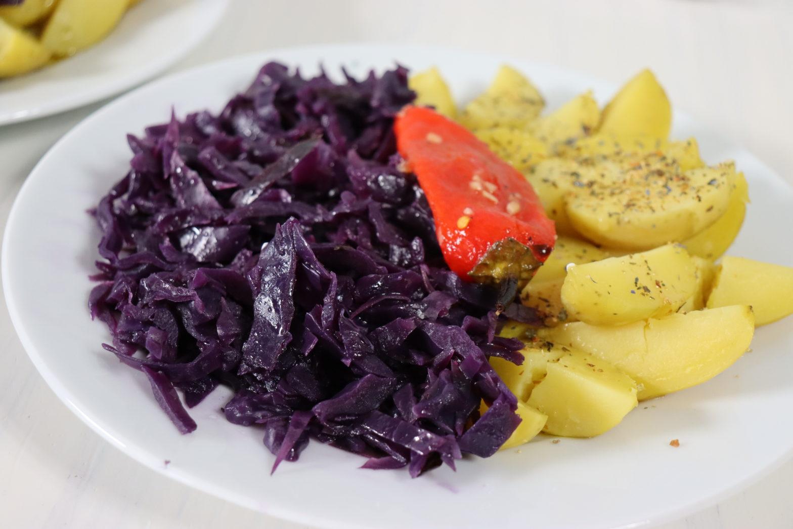 Teller mit Rotkohl, Pellkartoffel und eine rote , eingelegte Paprika