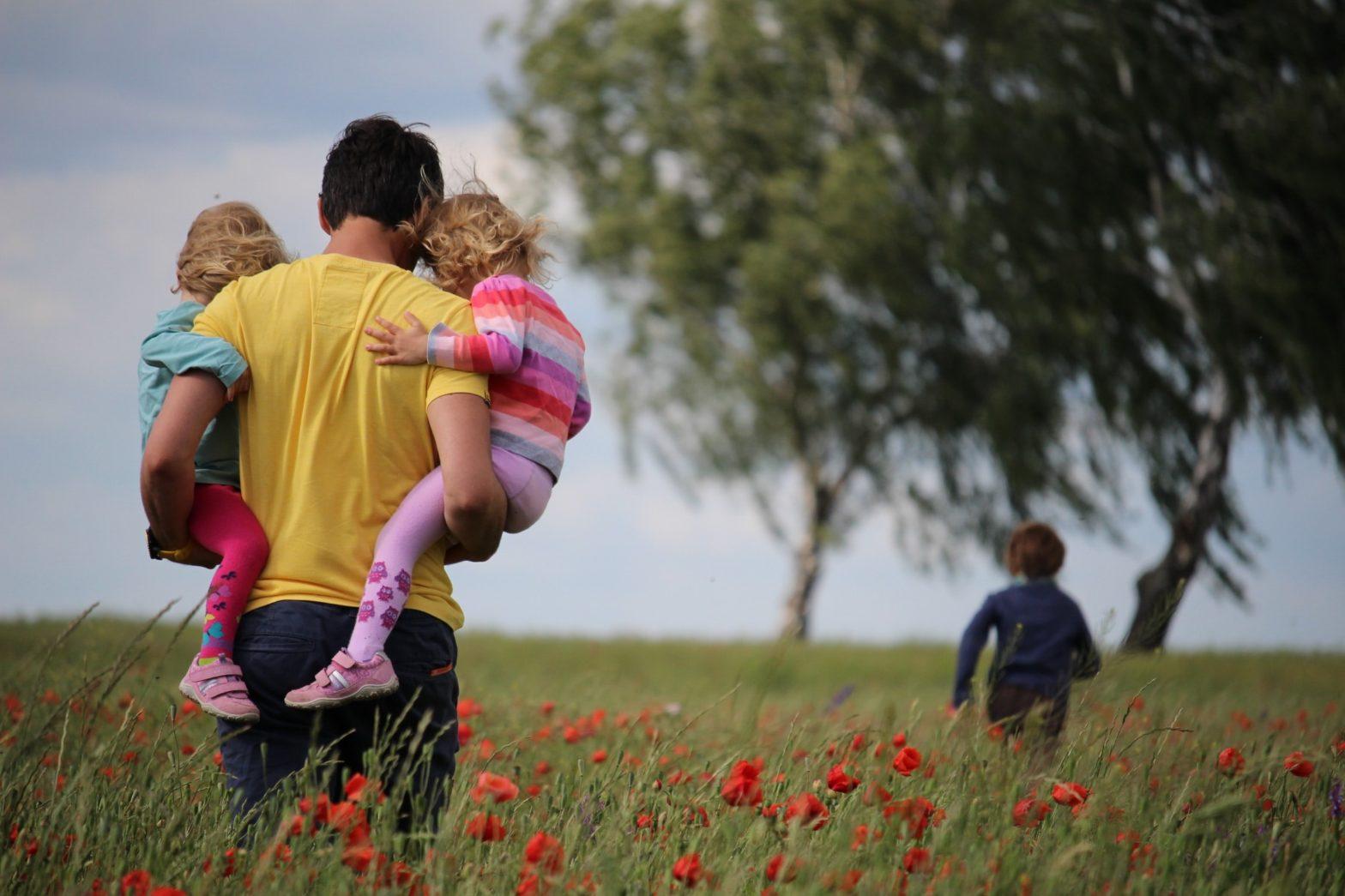 Ein Man der zwei Mädchen in dem Arm auf eine Wiese trägt.Im Vordergrund ist ein Baum und noch eine entfernte Person zu sehen.