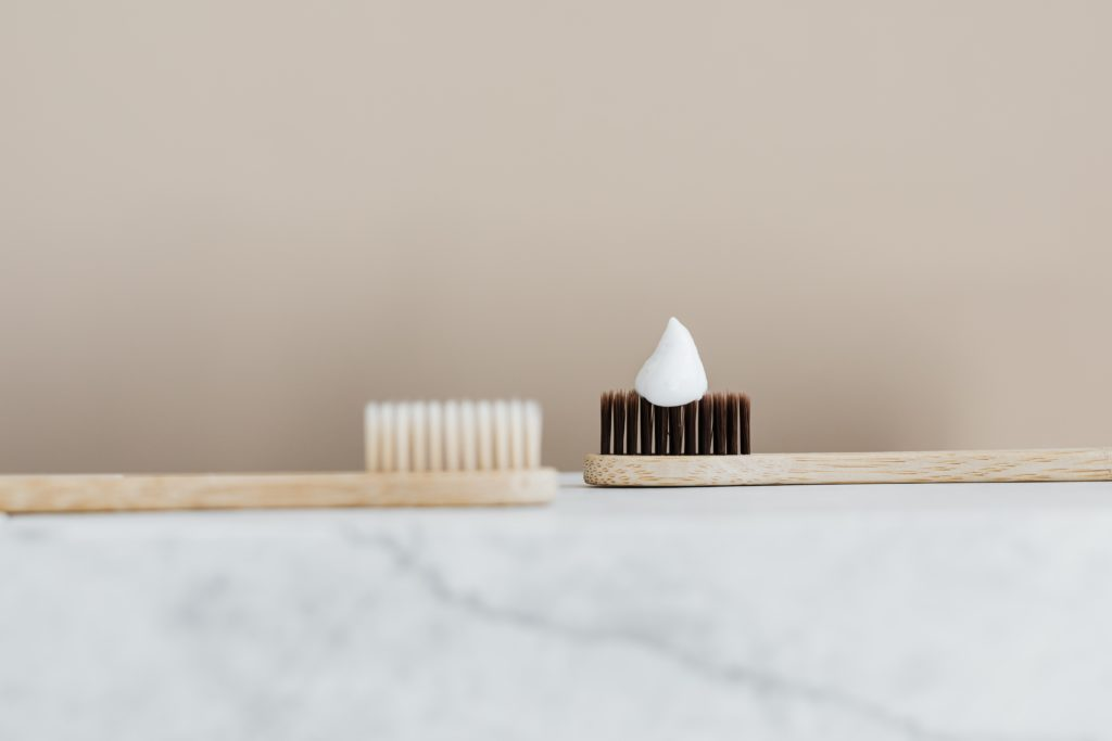 two bamboo toothbrushes. On the right side is one with bright brushes and on the left with dark brushes. On the top of the dark brush there is a small amount of toothpaste